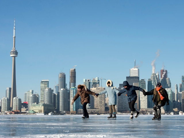TORONTO, ONTARIO: January 3, 2014-- ISLAND SKATE -- Skaters (FROM LEFT TO RIGHT) Tyler Hnatuk, Martha Farguar-McDonnell, Alec Farquar and Kathleen McDonnell, take to the frozen Toronto Harbor just off Algonquin Island with the city of Toronto in the background, Friday January 3, 2014.  [Peter J. Thompson/National Post]    [For Toronto story by Peter Kuitenbrower/Toronto]  //NATIONAL POST STAFF PHOTO
